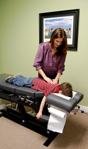 Dr. Dawes doing pediatric chiropractic care on a child
